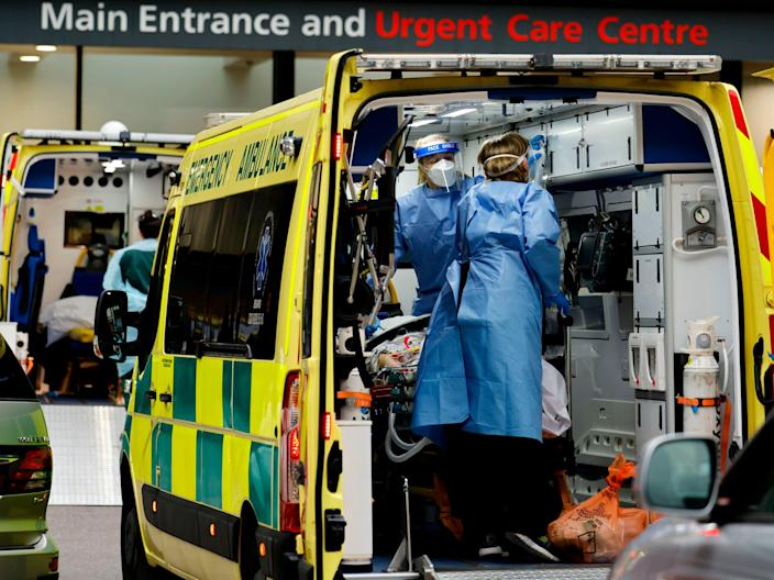 <p>Paramedics prepare to remove a patient from an ambulance as a new strain of coronavirus causes an upsurge in cases</p> (Getty)