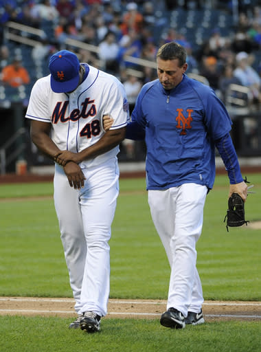 New York Mets relief pitcher Frank Francisco, left, holds his right wrist as he escorted off the field by a trainer after being hit by Miami Marlins' Logan Morrison's ground ball in the eighth inning of Game 1 of a baseball doubleheader at Citi Field, Saturday, Sept. 14, 2013, in New York. (AP Photo/Kathy Kmonicek)