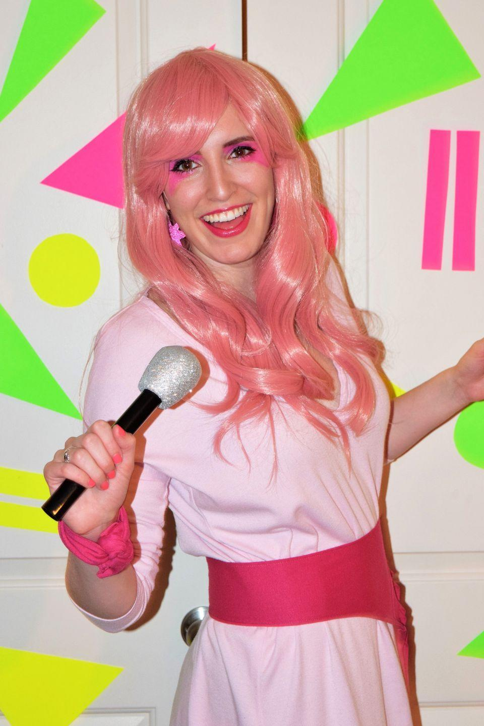 """<p>Glamour and glitter, fashion and fame! Make your '80s-kid dreams come true this Halloween by dressing up as Jem, the outrageous, pink-haired lead singer from the animated series <em>Jem and the Holograms. </em></p><p><strong>See more at <a href=""""https://sewbakedecorate.com/2016/05/24/80s-jem-and-the-holograms-costume-diy/"""" rel=""""nofollow noopener"""" target=""""_blank"""" data-ylk=""""slk:Sew Bake Decorate"""" class=""""link rapid-noclick-resp"""">Sew Bake Decorate</a>.</strong></p><p><a class=""""link rapid-noclick-resp"""" href=""""https://www.amazon.com/Jem-Holograms-color-PINK-Animation/dp/B0722ZFLKD?tag=syn-yahoo-20&ascsubtag=%5Bartid%7C2164.g.32645069%5Bsrc%7Cyahoo-us"""" rel=""""nofollow noopener"""" target=""""_blank"""" data-ylk=""""slk:SHOP PINK WIGS"""">SHOP PINK WIGS</a></p>"""