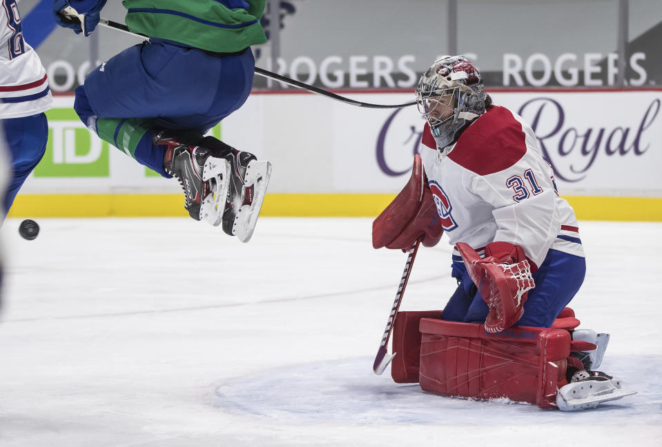 Montreal Canadiens goalie Carey Price makes a save as Vancouver Canucks' Brock Boeser jumps in front of him during the second period of an NHL hockey game Saturday, Jan. 23, 2021, Vancouver, British Columbia. (Darryl Dyck/The Canadian Press via AP)