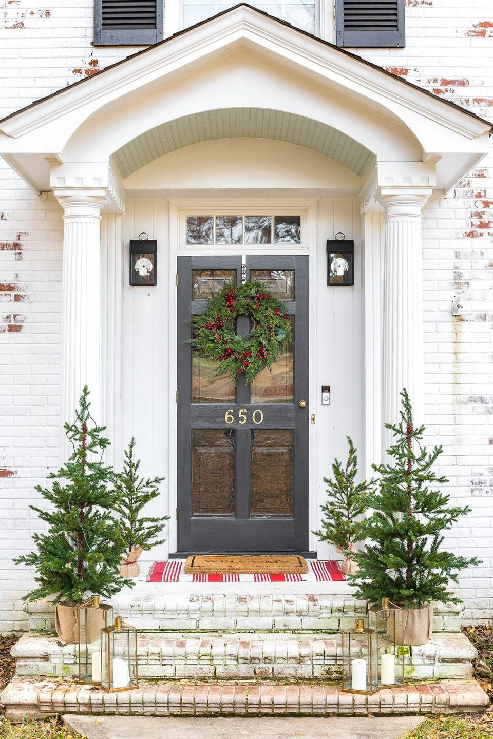 "<p>It's not just about the wreath: Line your front stoop with small trees to make guests feel warm and welcome. As a bonus, put a festive towel or blanket underneath the doormat for an unexpected pop of color.</p><p><em><a href=""https://www.blesserhouse.com/colonial-christmas-outdoor-decor/"" rel=""nofollow noopener"" target=""_blank"" data-ylk=""slk:Get the tutorial at Blesser House »"" class=""link rapid-noclick-resp"">Get the tutorial at Blesser House »</a></em></p>"