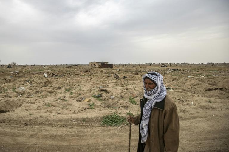 Farmer Hamad al-Ibrahim stands in his damaged fields in the eastern Syrian village of Baghouz