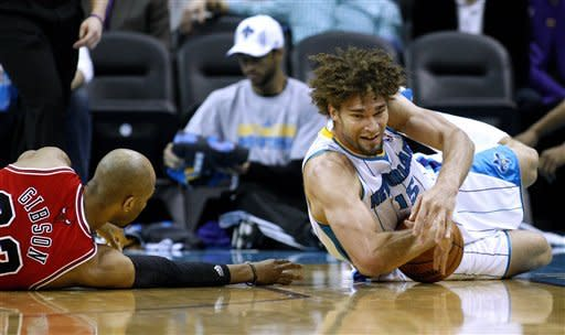 New Orleans Hornets center Robin Lopez (15) and Chicago Bulls forward Taj Gibson (22) go for a loose ball during the first half of an NBA basketball game in New Orleans, Tuesday, Feb. 19, 2013. (AP Photo/Jonathan Bachman)