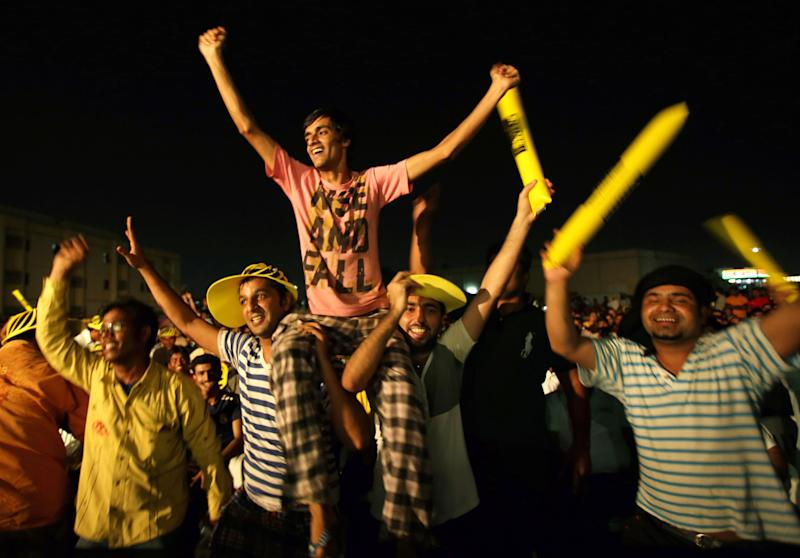 """In this Thursday, Oct. 10, 2013 photo, Asian laborers enjoy the final night of the Champ of the Camp, season seven of a singing contest for laborers, dubbed """"Dubai Idol"""" at the Sonapur Labor camp in Dubai, United Arab Emirates. A rare break from the laborers' routine comes in the form of Champ of the Camp, which combines quiz show speed, """"American Idol'' showmanship and movie trivia knowledge into a traveling roadshow that visits different camps each week around Dubai. (AP Photo/Kamran Jebreili)"""