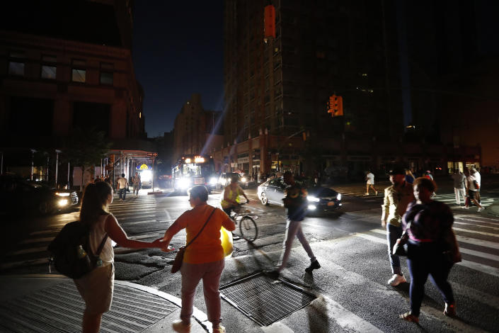 Pedestrians cross a dark street during a power outage, Saturday, July 13, 2019, in New York. (Photo: Michael Owens/AP)