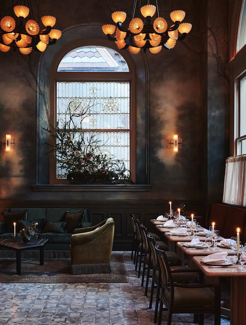The moody hand-painted forest-themed mural, by New York–based painter Dean Barger, gives a mystical vibe to the bar and lounge area.