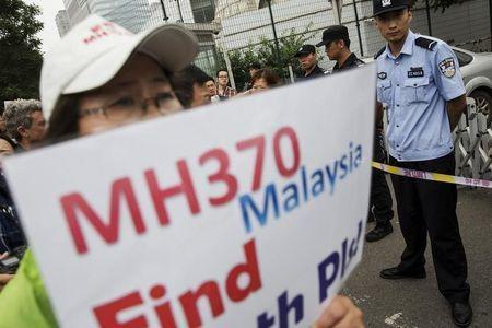 A woman whose relative was aboard Malaysia Airlines flight MH370 holds placard after police stopped protesting relatives from entering a road leading to the Malaysian embassy in Beijing