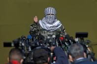 A Palestinian militant gestures as he speaks to the media during the first-ever joint exercise by Palestinian militant groups, in Gaza City