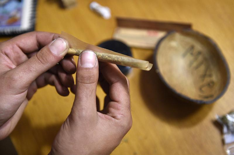A picture taken on July 9, 2014 shows a member of the Catalan Federation of Cannabis Association preparing a marijuana joint in Barcelona