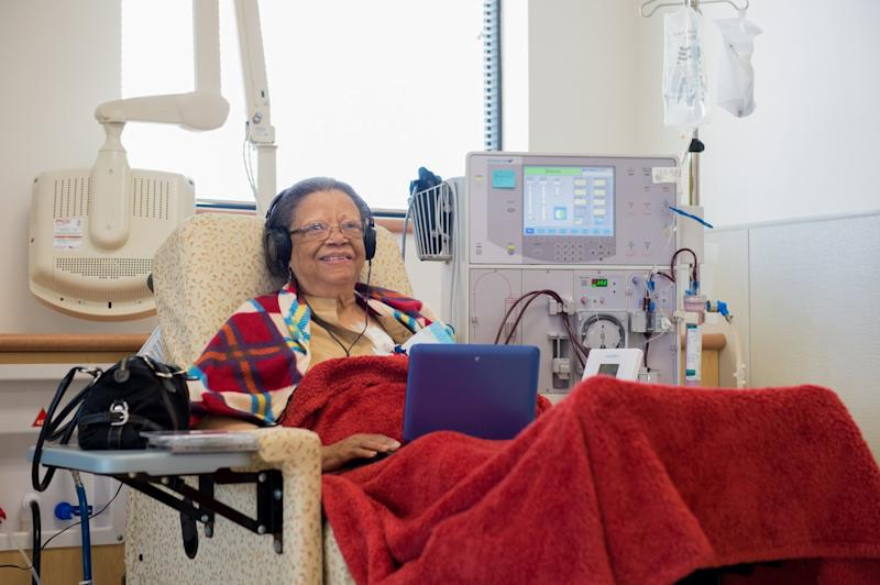 Woman reclining in an armchair and looking at a tablet, with medical equipment in background