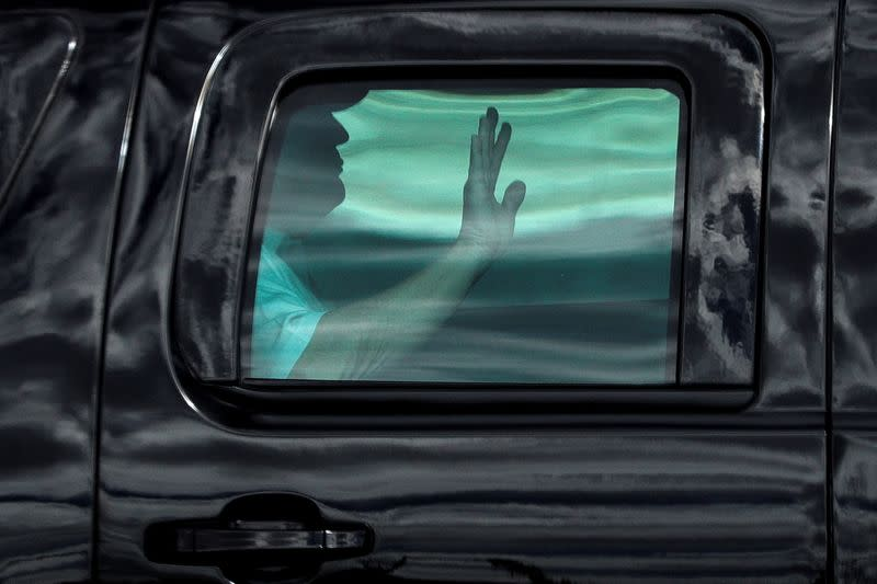 President Trump waves from his armored vehicle while departing from the Trump Golf Club in West Palm Beach