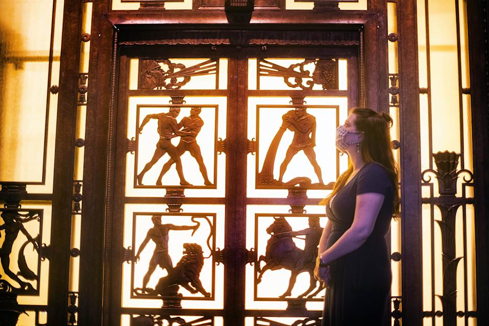 A woman looks at a bronze lift installed in department store Selfridges in 1928, at the Museum of London. Photo: PA