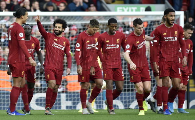 Liverpool's Mohamed Salah, 3rd left, celebrates with teammates after scoring his sides first goal during the English Premier League soccer match between Liverpool and Watford at Anfield stadium in Liverpool, England, Saturday, Dec. 14, 2019. (AP Photo/Rui Vieira)