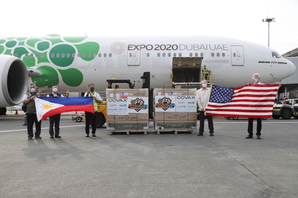 In this handout photo released by the National Task Force Against COVID19, US Embassy in the Philippines Chargé d'Affaires John C. Law, second from right, and Sean Callahan from US AID, right, holds a U.S. flag as Philippine vaccine czar Secretary Carlito Galvez Jr., center, and Health Secretary Francisco Duque II, second from left, hold the Philippine flag beside boxes containing Johnson & Johnson (J&J) vaccines as they arrive at Manila's International Airport, Philippines on Friday July 16, 2021. The first batch of vaccines consisting of 1,606,600 doses produced by American pharmaceutical firm Johnson & Johnson (J&J) and donated by the United States government through the COVAX facility have arrived in the country today. (National Task Force Against COVID19 via AP)