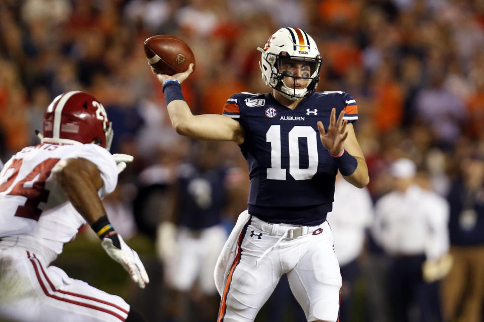 FILE - In this Nov. 30, 2019, file photo, Auburn quarterback Bo Nix (10) throws a pass as Alabama linebacker Terrell Lewis (24) pressures during the second half of an NCAA college football game in Auburn, Ala. Many major universities are determined to forge ahead despite warning signs about the virus, as evidenced by the expanding slate of college football games occurring Saturday. The football-obsessed SEC begins its season with fans in stadiums. (AP Photo/Butch Dill, File)