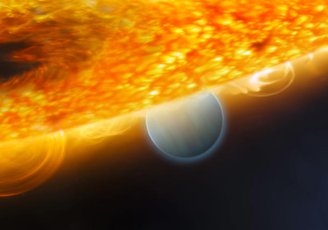 A handout photo from the European Space Agency released December 10, 2008 shows an artist's impression of the Jupiter-size extrasolar planet, HD 189733b, being eclipsed by its parent star. Astronomers using the Hubble Space Telescope have measured carbon dioxide and carbon monoxide in the planet's atmosphere. The planet is a ?hot Jupiter?, so close to its parent star that it completes an orbit in only 2.2 days. This type of observation is best carried out when the planet's orbit takes it behind the star (as seen from Earth), allowing for an opportunity to subtract the light of the star alone (when the planet is hidden behind it) from that of the star and planet together before an eclipse. This allows astronomers to isolate the infrared emission of the planet and carry out spectroscopic observations that chemically analyse the dayside atmosphere. REUTERS/ESA/NASA/M. Kornmesser (ESA/Hubble)/STScI.
