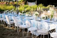 """""""The main wedding table draped in 'La Vie en Rose' linen LoveShackFancy tablecloth and napkins in morning gray. This is one of my favorite shots because the sun really enriches the natural colors of the field and beautiful indigo's and whites of the tablescape,"""" Deans says."""