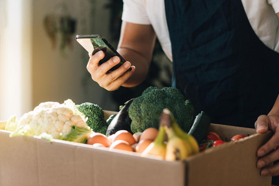 Cropped shot of man using smart phone to order vegetables and fruits delivery online