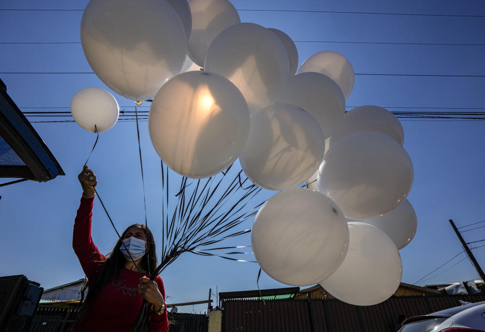 An organ grinder prepares white balloons for release during the funeral of 93-year-old Hector Lizana, who died from COVID-19, three weeks after his son Manuel also died from COVID-19, at a cemetery in Santiago, Chile, Wednesday, Sept.15, 2021. (AP Photo/Esteban Felix)