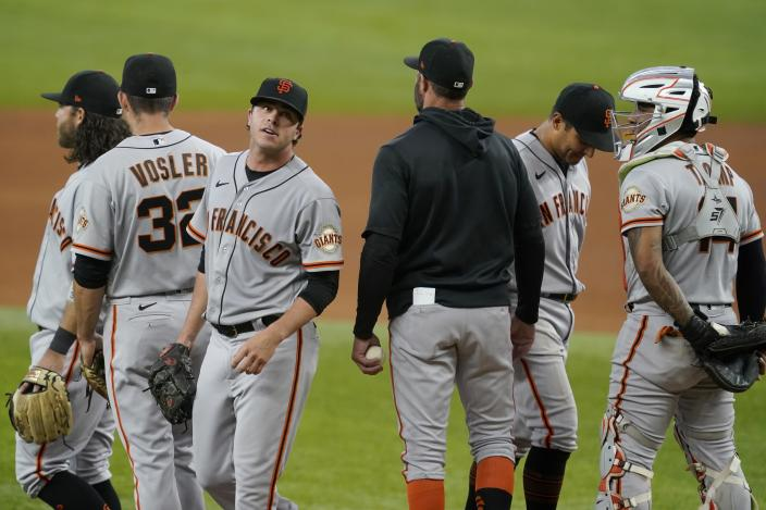 San Francisco Giants relief pitcher Sammy Long, third from left, leaves the mound after turning over the ball to manager Gabe Kapler, blue jacket, as Brandon Crawford, left rear, Jason Vosler (32), Donovan Solano, second from right, and Chadwick Tromp, right, stand by in the sixth inning of a baseball game against the Texas Rangers in Arlington, Texas, Wednesday, June 9, 2021. (AP Photo/Tony Gutierrez)