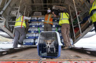"""Workers unload kennels of dogs and cats from a cargo plane after the landing of a """"Paws Across the Pacific"""" pet rescue flight Thursday, Oct. 29, 2020, in Seattle. Volunteer organizations flew more than 600 dogs and cats from shelters across Hawaii to the U.S. mainland, calling it the largest pet rescue ever. The animals are being taken from overcrowded facilities in the islands to shelters in Washington state, Oregon, Idaho, and Montana. (AP Photo/Elaine Thompson)"""