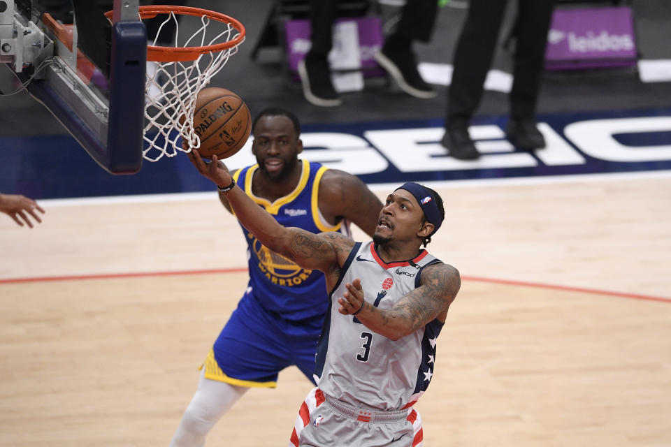 Washington Wizards guard Bradley Beal (3) goes to the basket past Golden State Warriors forward Draymond Green, back, during the first half of an NBA basketball game, Wednesday, April 21, 2021, in Washington. (AP Photo/Nick Wass)