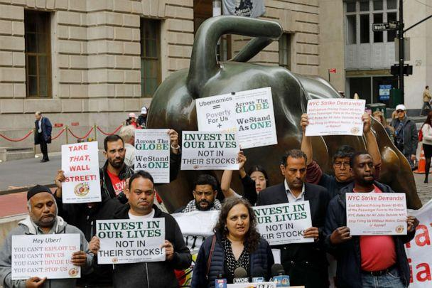 PHOTO: Uber drivers protest next to the Charging Bull statue in New York's financial district, May 8, 2019. The protests arrive just ahead of Uber's initial public stock offering, which is planned for Friday.  (Mark Lennihan/AP)