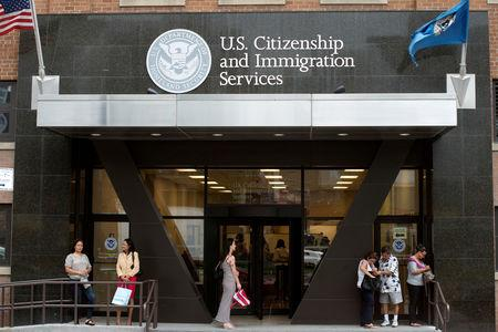 FILE PHOTO: People stand on the steps of the U.S. Citizenship and Immigration Services offices in New York, August 15, 2012. REUTERS/Keith Bedford/File Photo