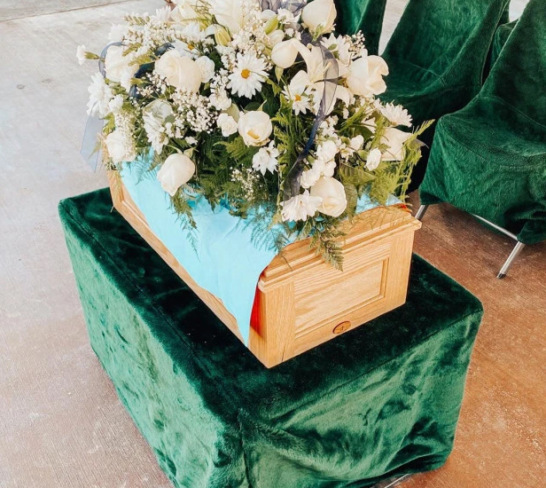 Pictured is the coffin of baby Crew with flowers on top on a platform covered by a green felt sheet.