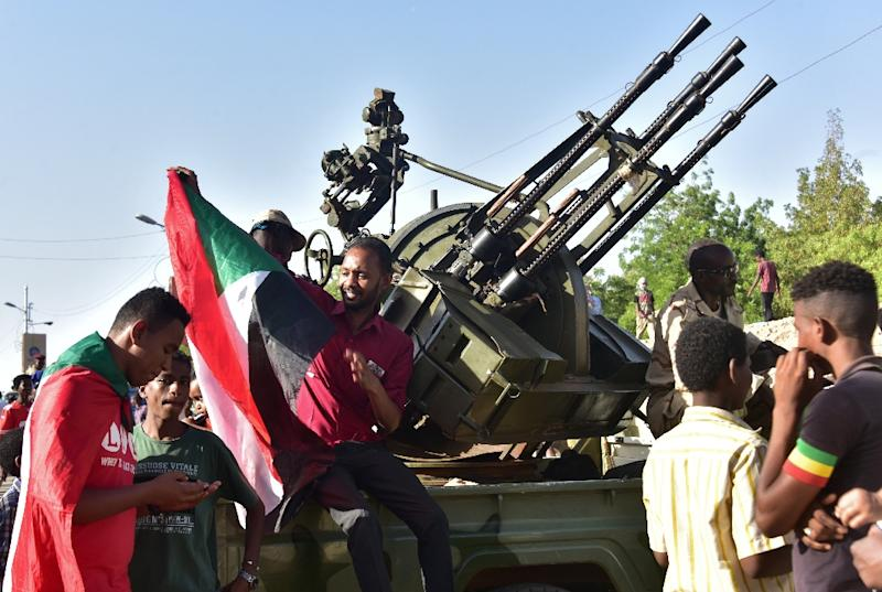 Young Sudanese sit atop a military vehicle as the country's second new military leader in as many days announced on April 13, 2019 the release of prisoners, the lifting of a curfew, and other measures (AFP Photo/AHMED MUSTAFA)