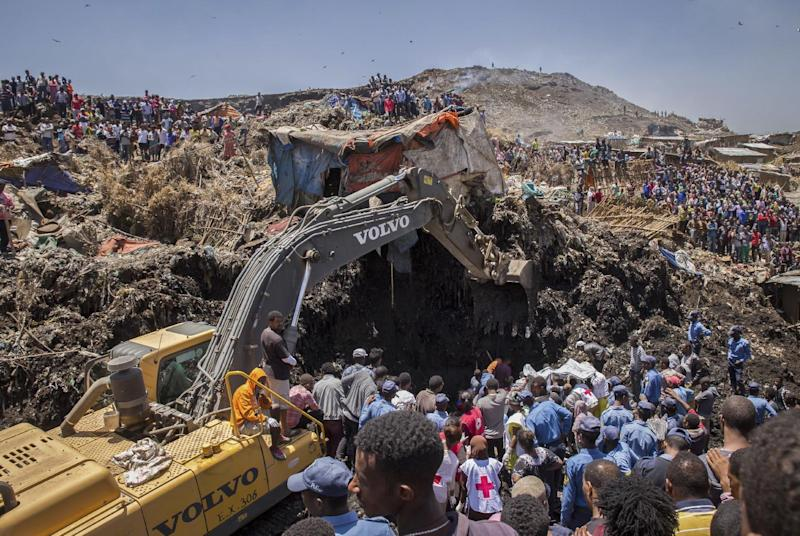 In this Sunday, March 12, 2017 photo, rescuers work at the scene of a garbage landslide, on the outskirts of the capital Addis Ababa, in Ethiopia. A mountain of trash gave way in a massive garbage dump on the outskirts of Ethiopia's capital, killing dozens and leaving more missing, residents said. (AP Photo/Mulugeta Ayene)
