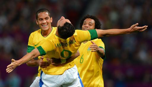 Brazil's forward Leandro Damiao (C) celebrates with Brazil's defender Romulo (L) and Brazil's defender Marcelo after scoring the third goal during the London 2012 Olympic Games mens semi final football match between Brazil and South Korea at Old Trafford in Manchester, north-west England on August 7, 2012. AFP PHOTO / ANDREW YATES