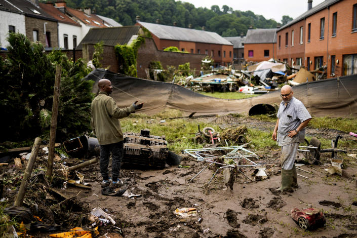 Image: Two residents talk to each other as they clean up after flooding in Ensival, Verviers, Belgium, July 16, 2021 (Francisco Seco / AP)
