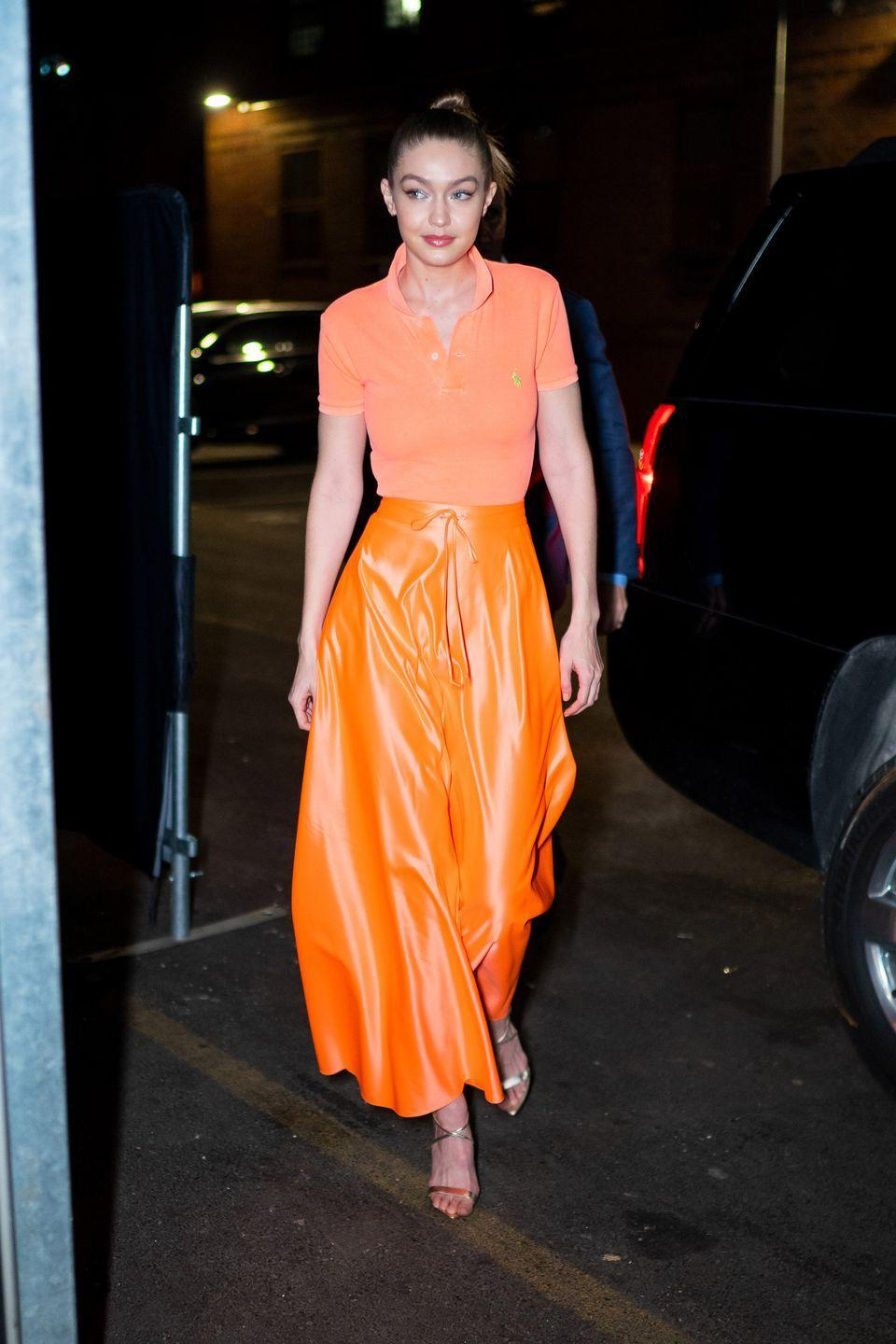 <p>In an orange Ralph Lauren polo, tonal maxi skirt, and strappy sandals. </p>