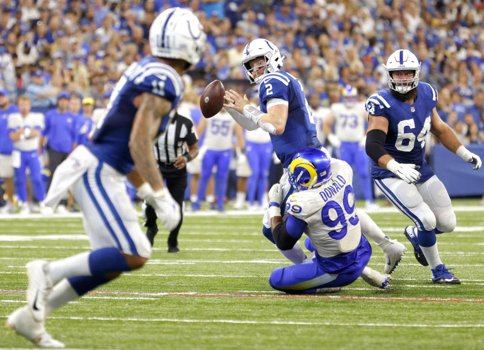 INDIANAPOLIS, INDIANA - SEPTEMBER 19: Quarterback Carson Wentz #2 of the Indianapolis Colts looks to throw the ball while being tackled by defensive end Aaron Donald #99 of the Los Angeles Rams in the game at Lucas Oil Stadium on September 19, 2021 in Indianapolis, Indiana. (Photo by Michael Hickey/Getty Images)