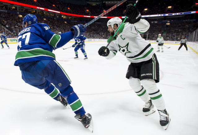 Vancouver Canucks defenseman Tyler Myers (57) and Dallas Stars left wing Jamie Benn watch the puck during the second period of an NHL hockey game Thursday, Nov. 14, 2019, in Vancouver, British Columbia. (Jonathan Hayward/the Canadian Press via AP)