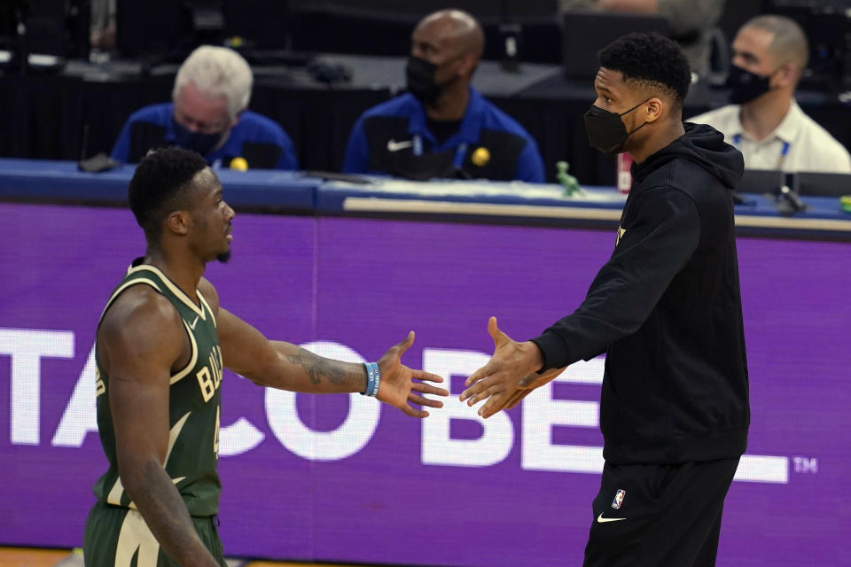 Injured Milwaukee Bucks forward Giannis Antetokounmpo, right, greets forward Thanasis Antetokounmpo during the first half of an NBA basketball game against the Golden State Warriors in San Francisco, Tuesday, April 6, 2021. (AP Photo/Jeff Chiu)