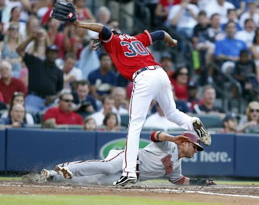 Arizona Diamondbacks' Martin Prado, bottom, scores on a wild pitch as Atlanta Braves starting pitcher Ervin Santana (30) covers the plate in the second inning of a baseball game in Atlanta, Friday, July 4, 2014. (AP Photo/John Bazemore)
