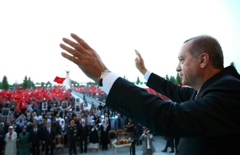 Turkish President Recep Tayyip Erdogan waves to the crowd during the opening ceremony of the July 15 Martyrs' Monument, at the Presidential Complex in Ankara, on July 16, 2017