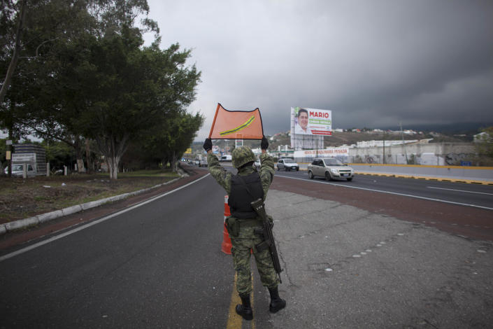 In this photo taken on Thursday, June 21, 2012, an Army soldier signals cars to reduce their speed at a checkpoint on a highway entering Cuernavaca, Mexico. As Mexicans head to the ballot box Sunday, drug cartels are registering their votes with scare tactics and cold, hard cash to make sure whoever is elected doesn't interfere with their lucrative operations. (AP Photo/Alexandre Meneghini)