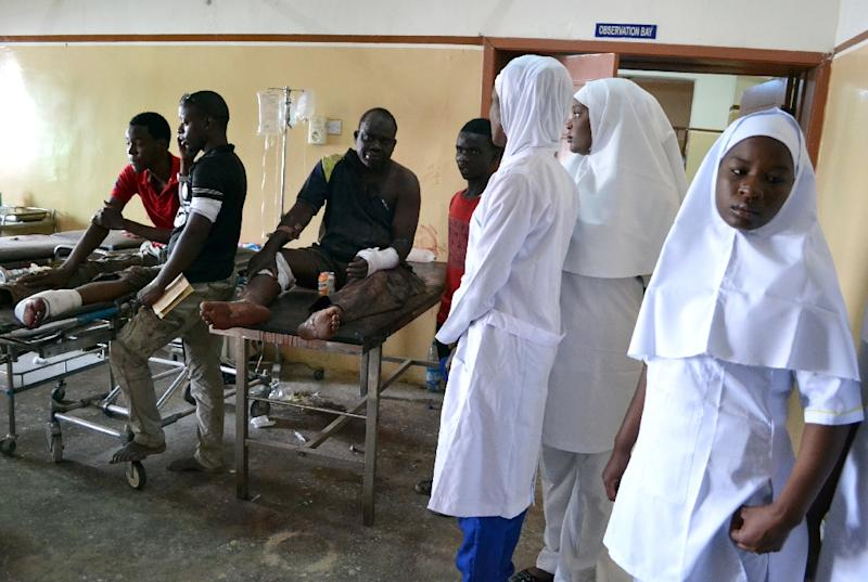 Nurses stand next to victims of the multiple blasts blamed on Boko Haram at the State Specialist Hospital in Maiduguri, on September 21, 2015