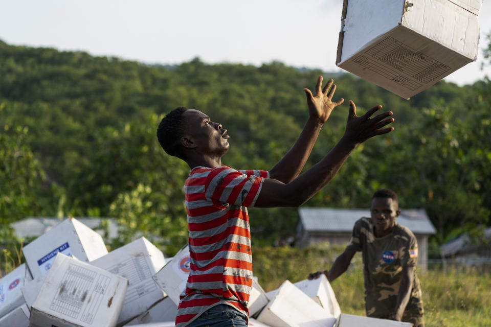 """A Haitian aid worker catches a hygiene kit while unloading a VM-22 Osprey at Jeremie Airport, Saturday, Aug. 28, 2021, in Jeremie, Haiti. The VMM-266, """"Fighting Griffins,"""" from Marine Corps Air Station New River, from Jacksonville, N.C., are flying in support of Joint Task Force Haiti after a 7.2 magnitude earthquake on Aug. 22, caused heavy damage to the country. (AP Photo/Alex Brandon)"""