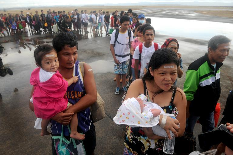 Typhoon survivor Rosel Honrado (R), 24, carries her one-day-old son Ian Daniel as they take a flight on a C-130 military plane out of Tacloban in the Philippines on November 13, 2013