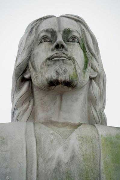 "The ""Christ of the Pacific"" statue appears neglected and dirty, in stark contrast to two military monuments located nearby"