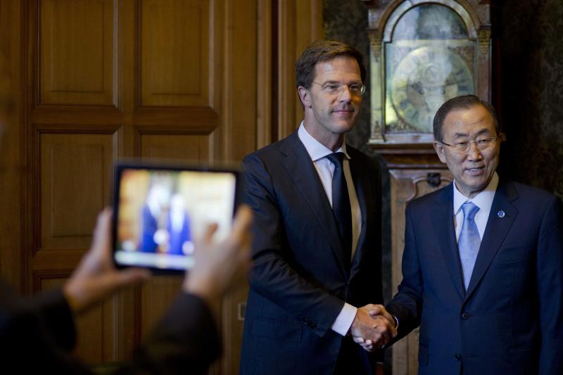 A delegation member takes pictures with an iPad as U.N. Secretary General Ban Ki-moon, right, shakes hands with Dutch Prime Minister Mark Rutte at the start of a bilateral meeting ahead of celebrations marking the 100th anniversary of the UN Peace Palace in The Hague, Netherlands, Wednesday, Aug. 28, 2013. (AP Photo/Peter Dejong, Pool)