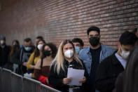 People line up outside a club to be screened for the coronavirus ahead of a music concert in Barcelona, Spain, Saturday, March 27, 2021. Five thousand music lovers are set to attend a rock concert in Barcelona on Saturday after passing a same-day COVID-19 screening to test its effectiveness in preventing outbreaks of the virus at large cultural events. The show by Spanish rock group Love of Lesbian has the special permission of Spanish health authorities. While the rest of the country is limited to gatherings of no more than four people in closed spaces, the concertgoers will be able to mix freely while wearing face masks. (AP Photo/Emilio Morenatti)