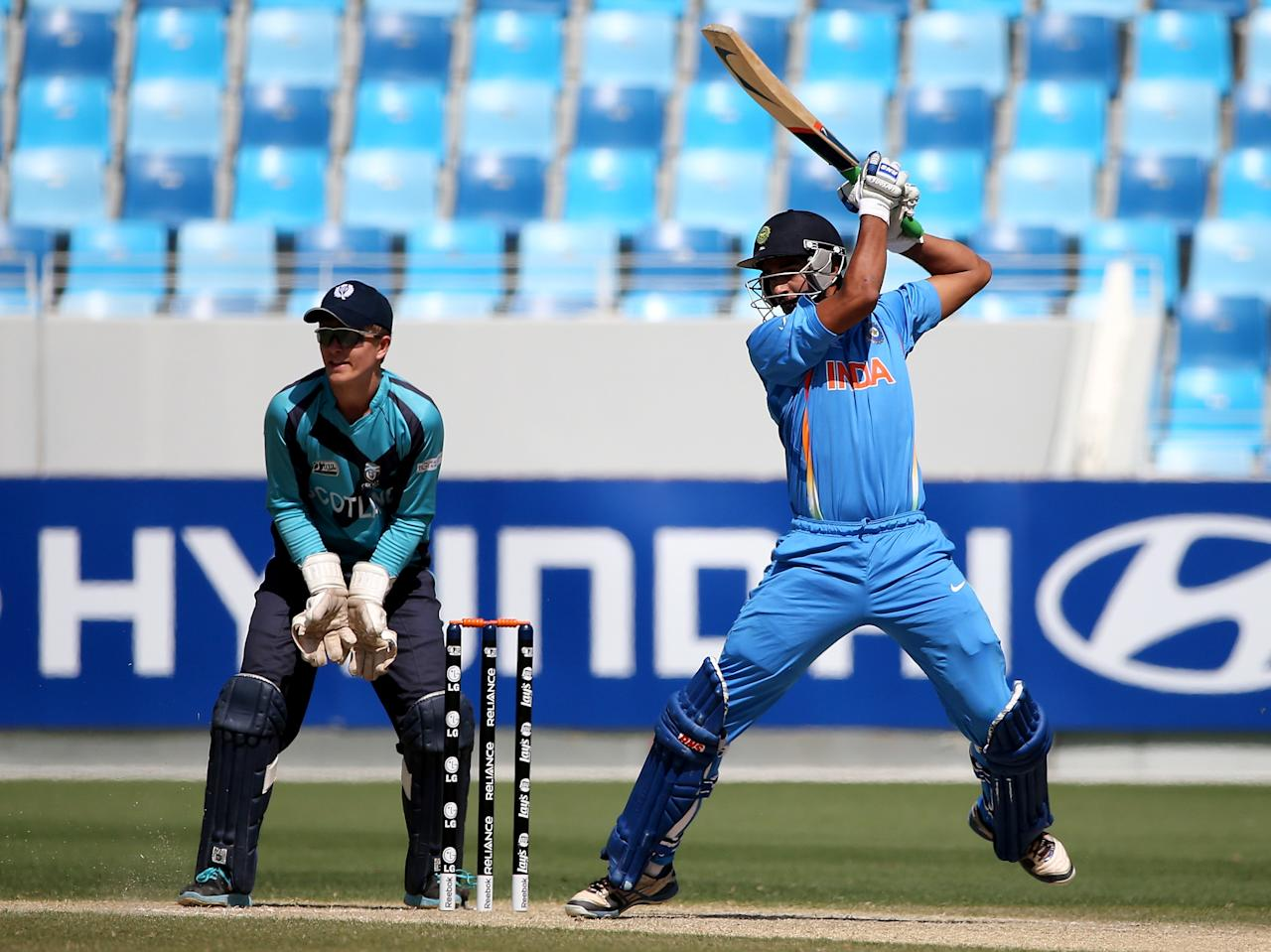 DUBAI, UNITED ARAB EMIRATES - FEBRUARY 17:  Deepak Hooda of India bats as Alex Baum looks on during the ICC U19 Cricket World Cup 2014 match between India and Scotland at the Dubai Sports City Cricket Stadium on February 17, 2014 in Dubai, United Arab Emirates.  (Photo by Francois Nel - IDI/IDI via Getty Images)