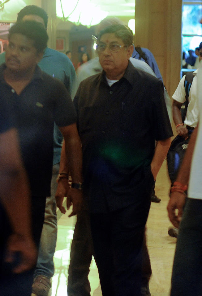 Board of Control for Cricket in India (BCCI) President, N Srinivasan (2R) is pictured through glass as he leaves an emergency meeting at a hotel in Chennai on June 2, 2013.  India's cricket chief Sunday defied calls to quit over a betting scandal in the country's top domestic competition but agreed to step aside to allow an investigation to take place, the board announced.  AFP PHOTO        (Photo credit should read STR/AFP/Getty Images)