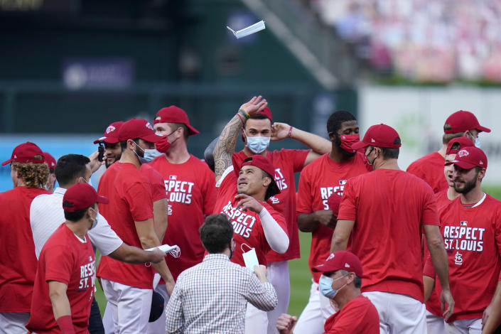 St. Louis Cardinals' Kolten Wong throws a face mask in the air as he celebrates with teammates after defeating the Milwaukee Brewers in a baseball game to earn a playoff birth Sunday, Sept. 27, 2020, in St. Louis. (AP Photo/Jeff Roberson)