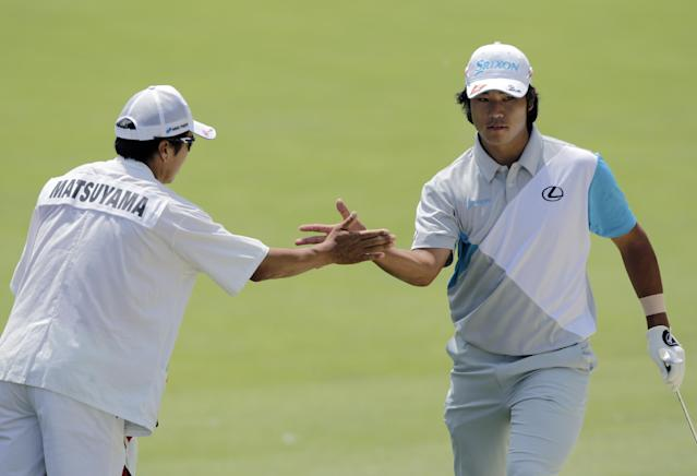 Hideki Matsuyama, right, of Japan, celebrates with his caddie after holing out from the sand on the second hole during the final round of the Memorial golf tournament, Sunday, June 1, 2014, in Dublin, Ohio. (AP Photo/Jay LaPrete)